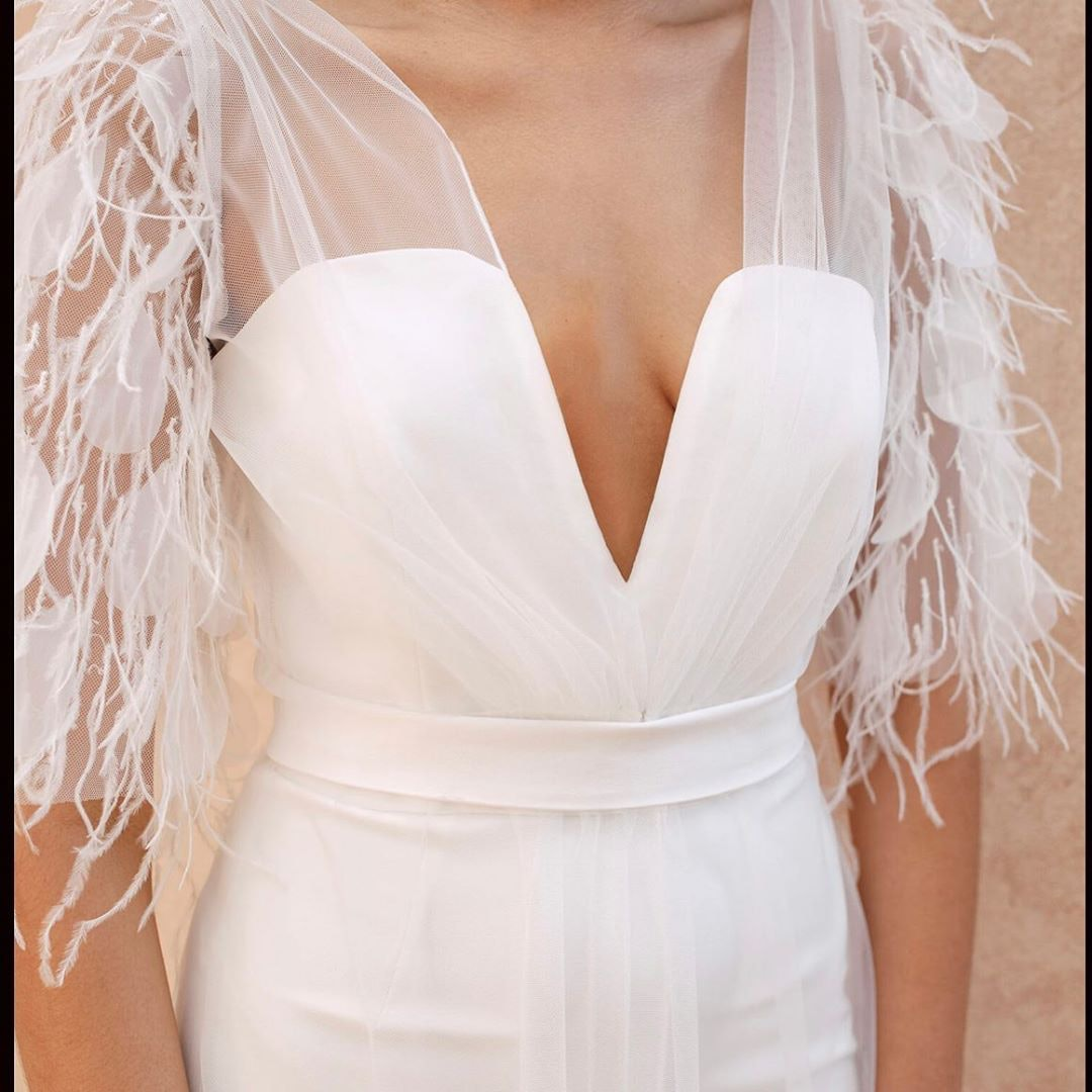 Close up shot of brides dress with feathers on the sleeves
