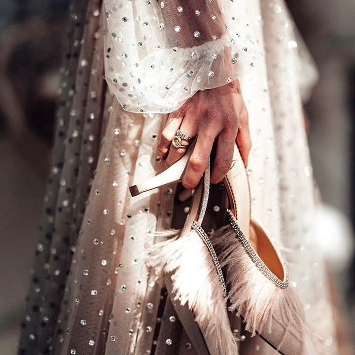 Bride holding shoes in her hands, shoes have feathers on them