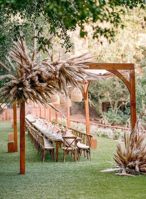 Outdoor wooden arbour with pampas grass hanging on the sides