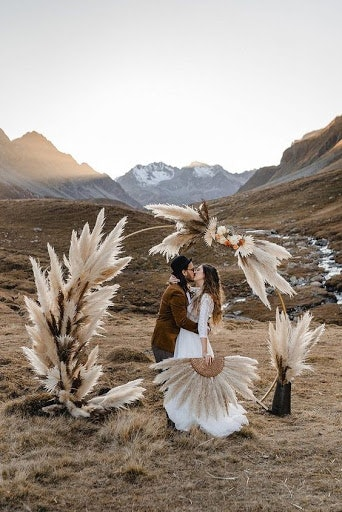 Bride and groom standing under pampas arbor kissing with mountains in the background