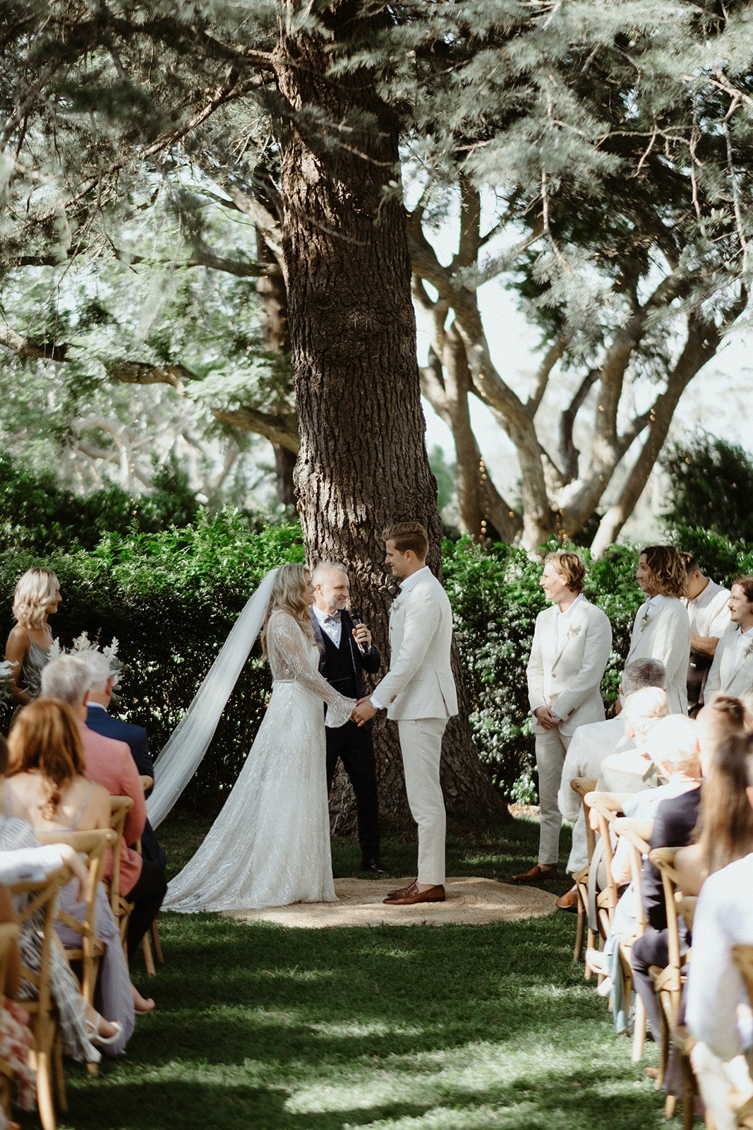 Bride and groom standing under tree holding hands