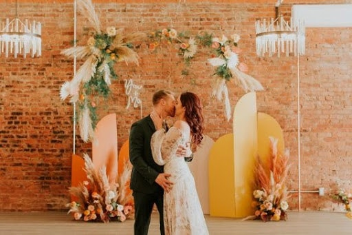 Bride and groom kissing in front of geometric shaped arbor with pampas grass