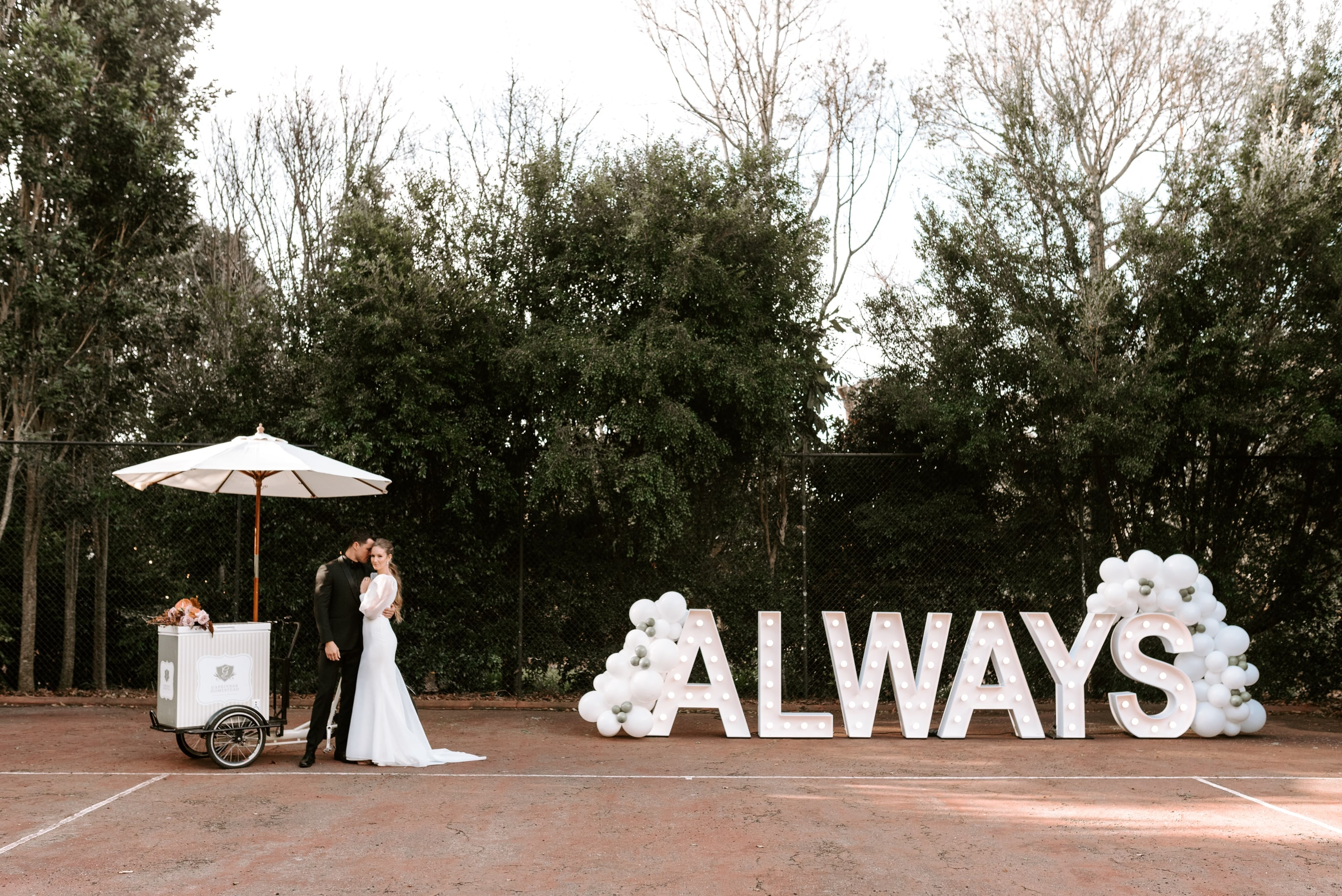 Light-up sign that says 'ALWAYS' decorated with balloons with a bride and groom standing next to it