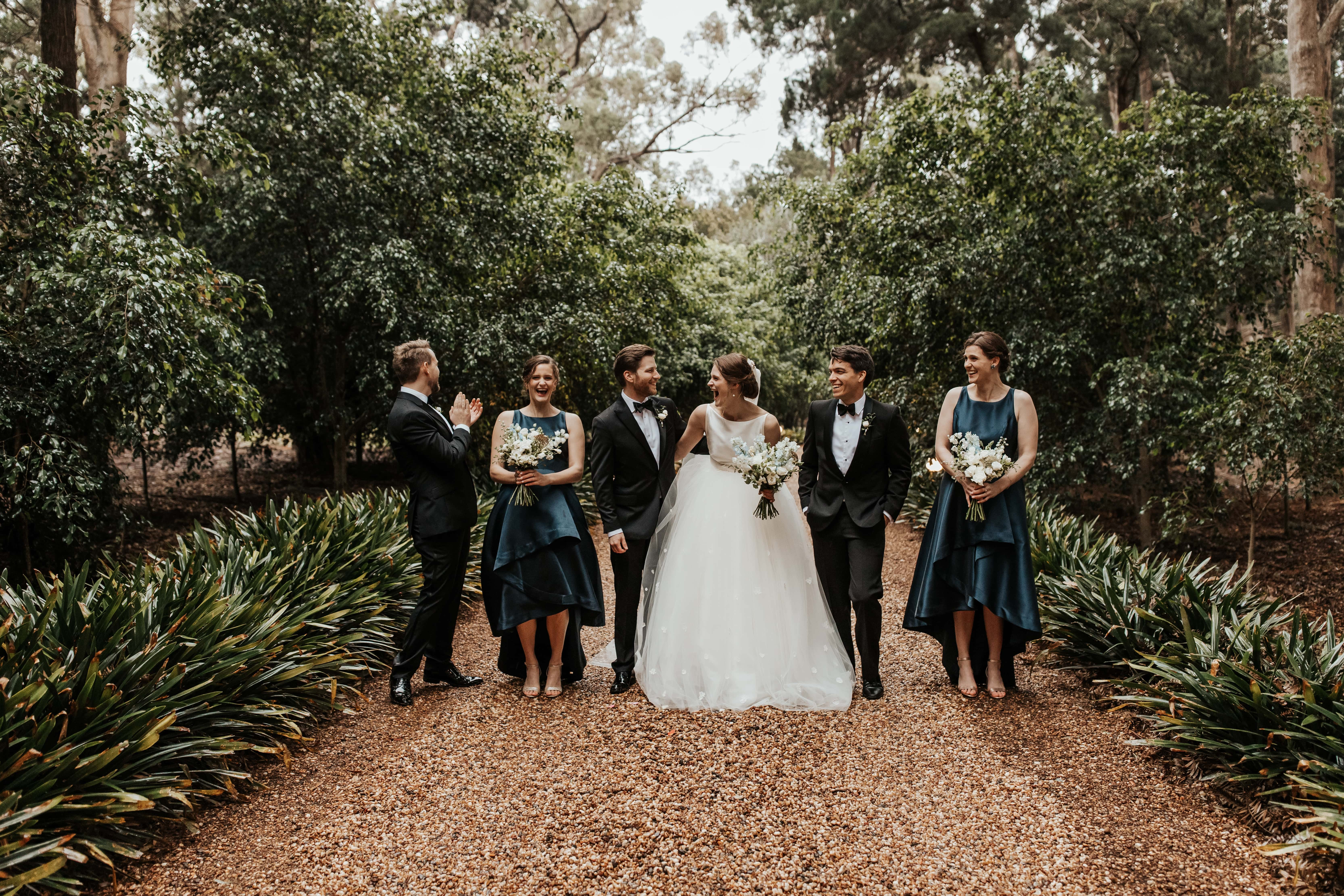 Couple laughing with bridal party on driveway