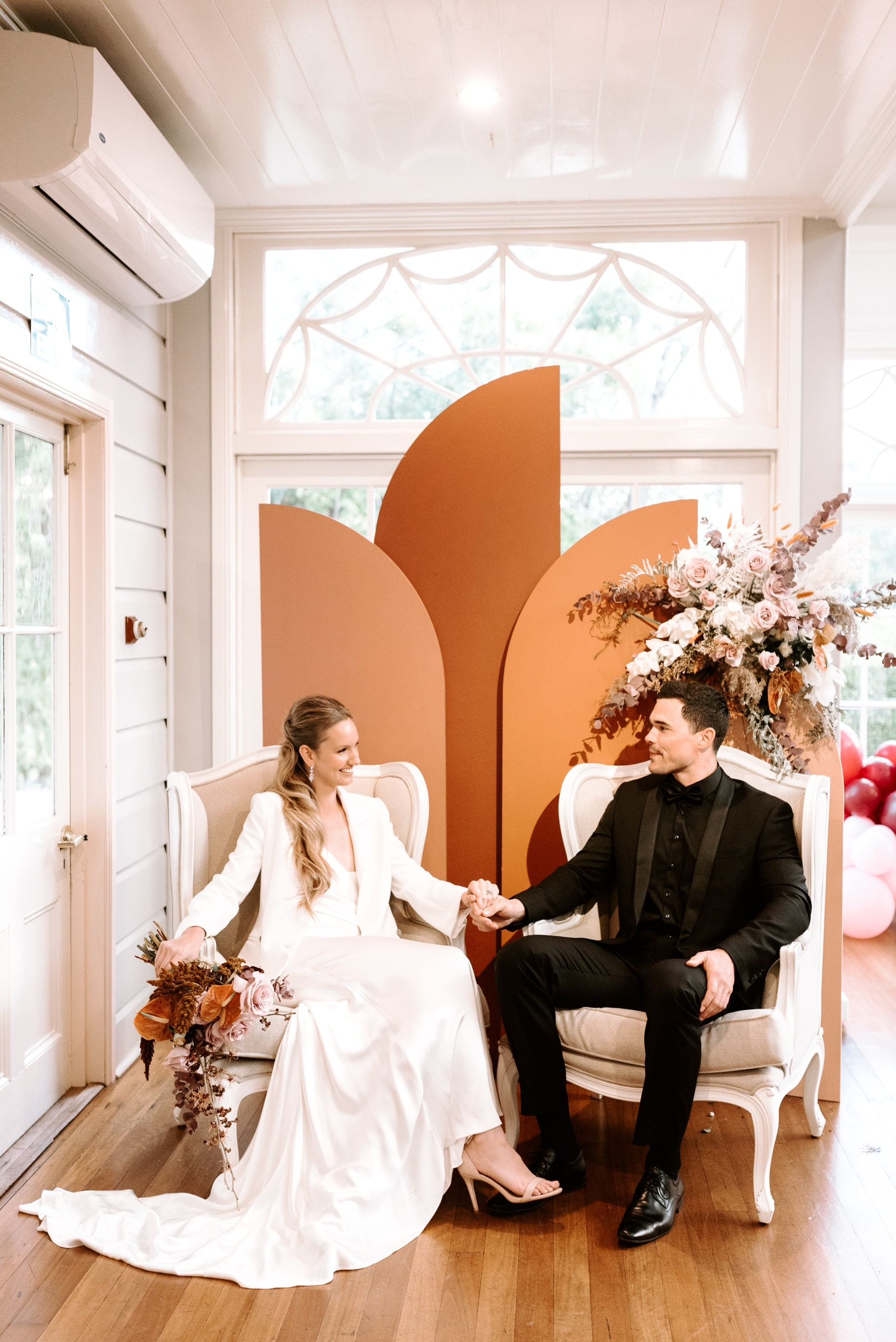 Bride and groom sitting on chairs holding hands with colourful arch backdrop