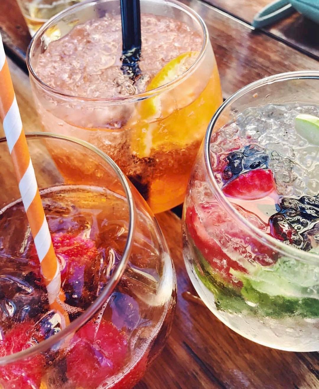 Three drinks with ice and fruit inside