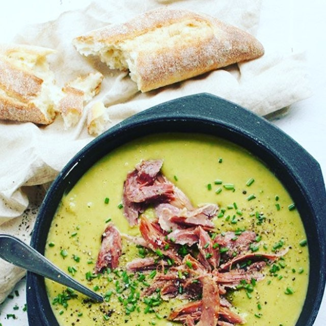 Pea and Ham soup with prosciutto on top and sourdough bread in the background