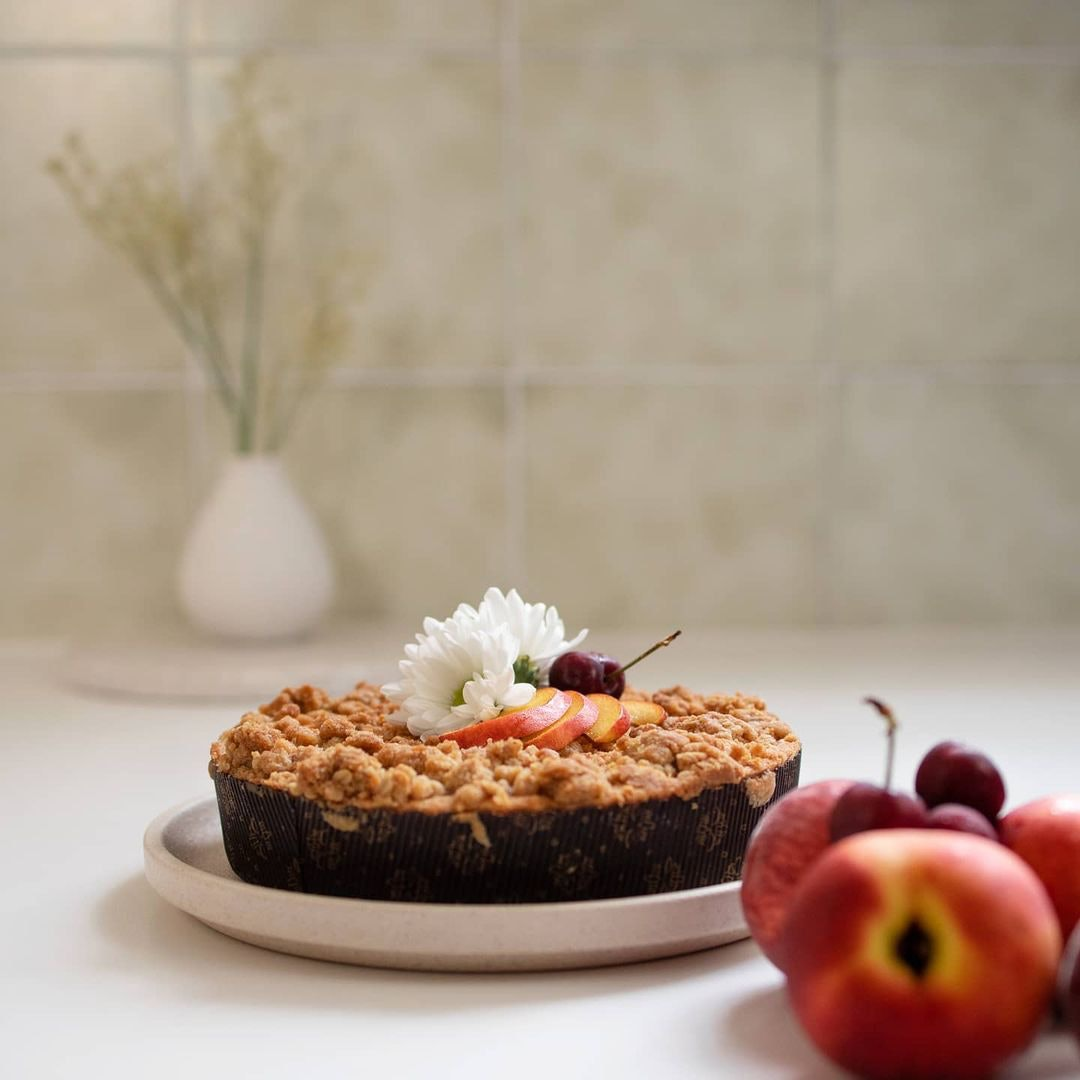 Apple tart with flowers and fruit on top and pieces of fruit on the side