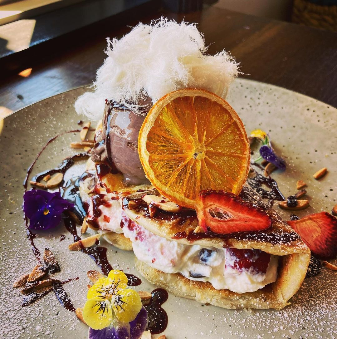 Crepe filled with berries and creme with glazed orange on top and fairy floss