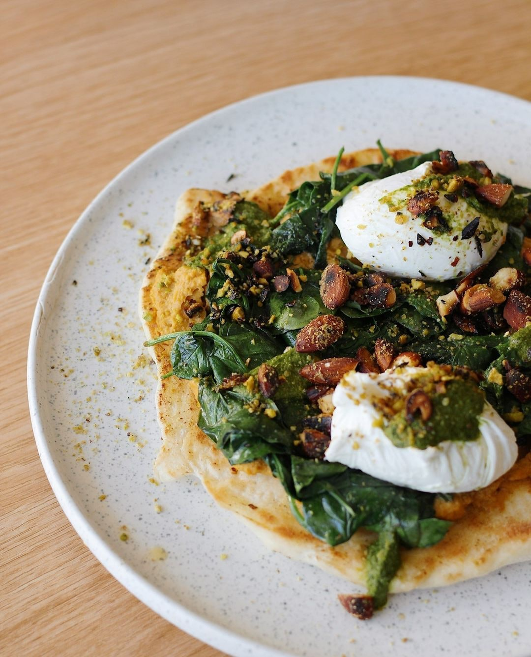 Crepe with poached eggs on top and spinach and eastern spices