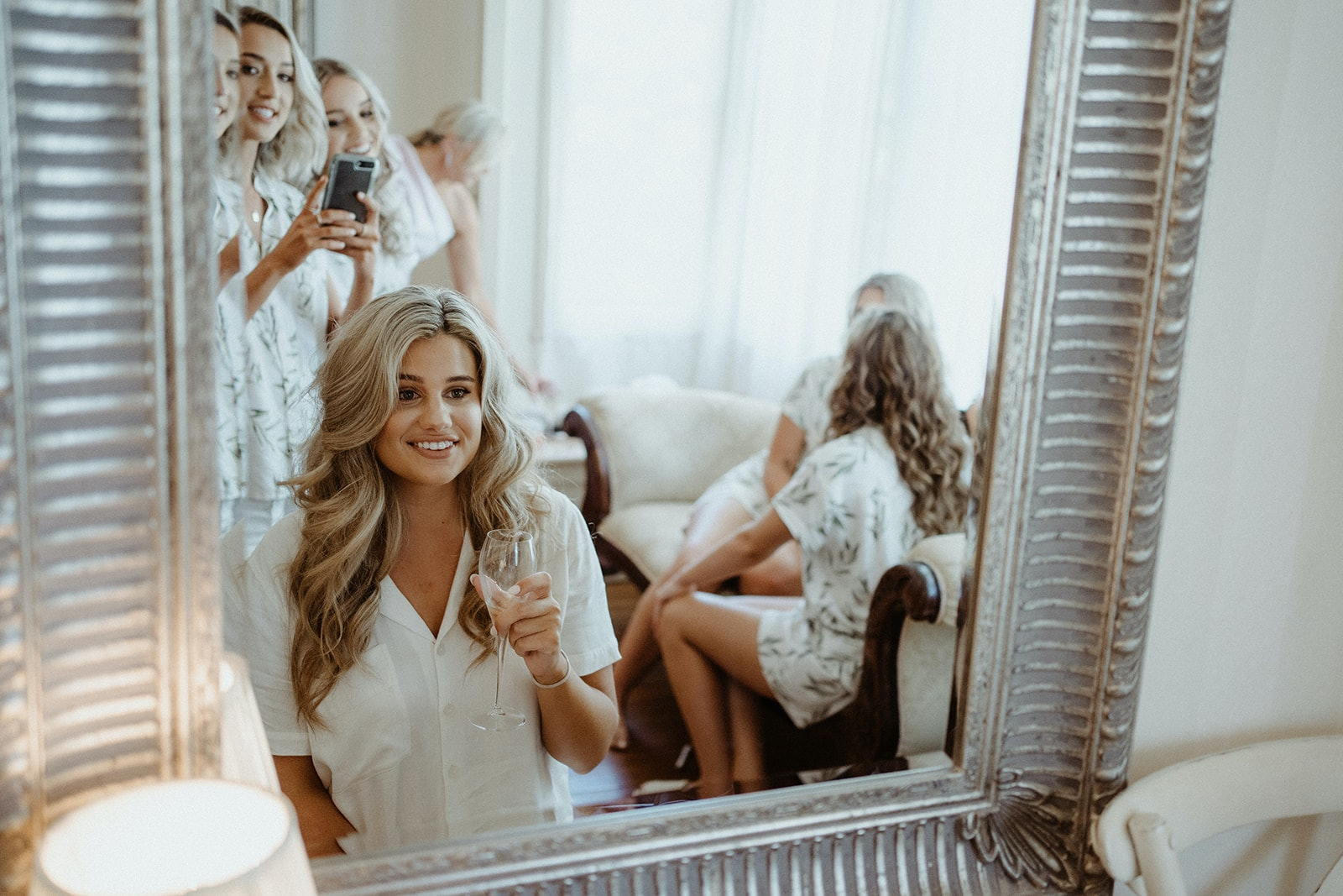 Bride looking in mirror holding a champagne glass