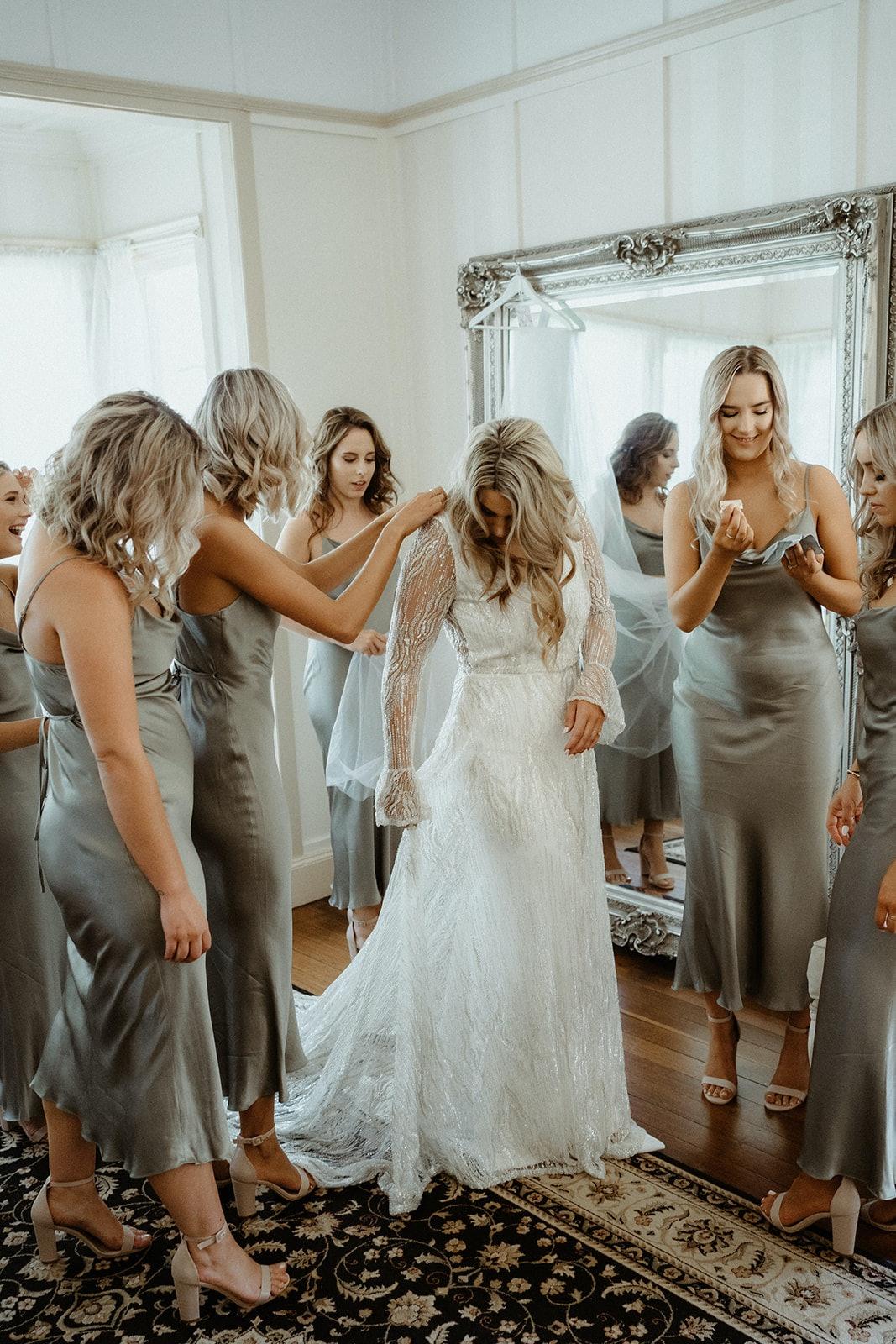 Bride getting ready in Bride's retreat with bridesmaids
