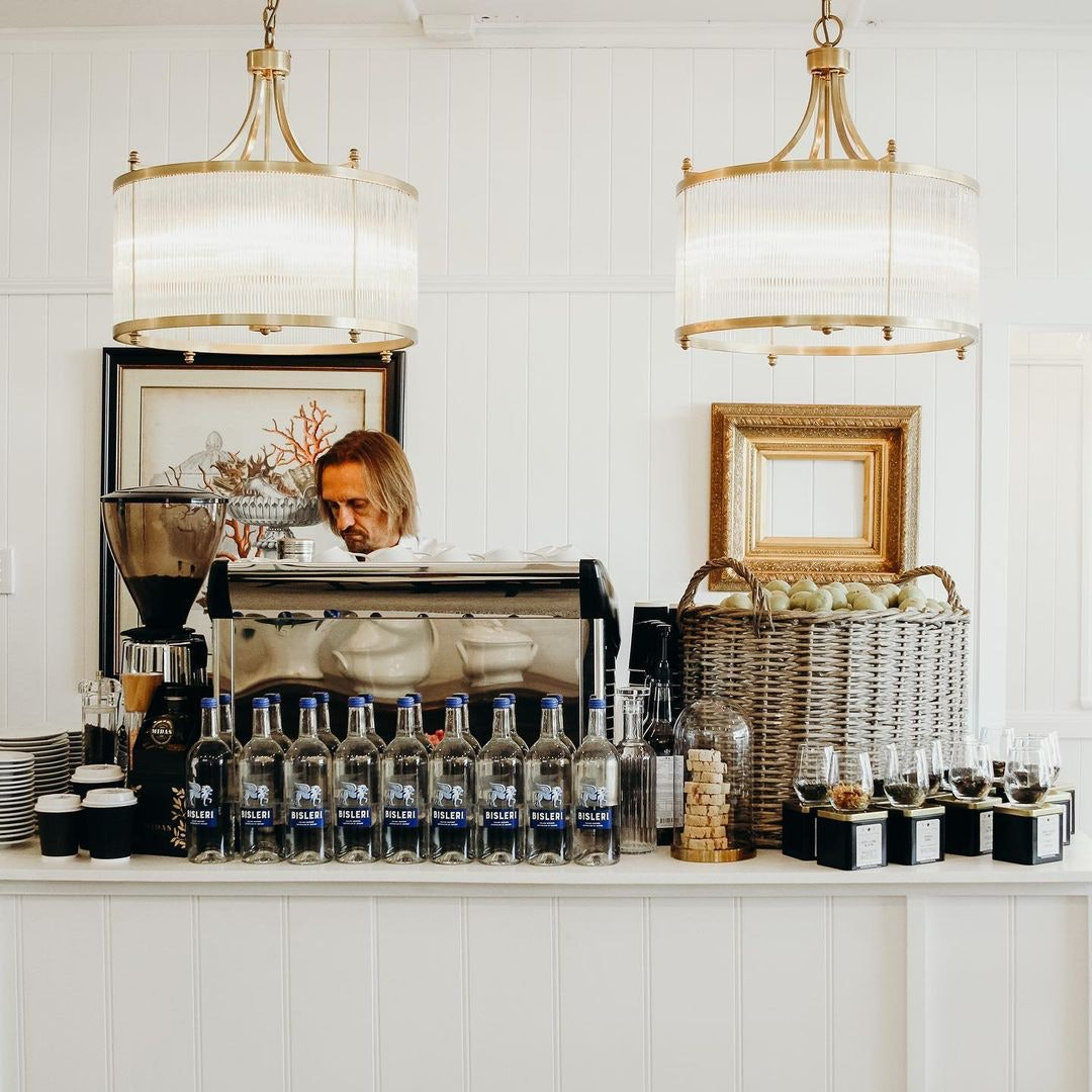 Coffee machine with overhanging gold and white pendants
