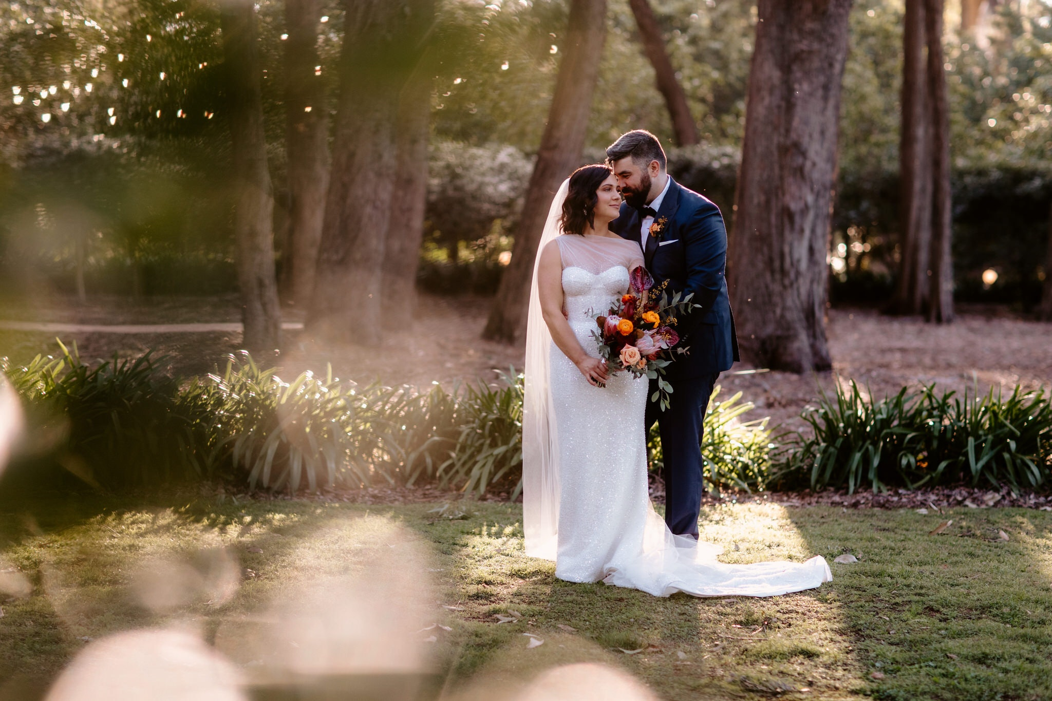 Bride and groom standing close together in gardens posing romantically