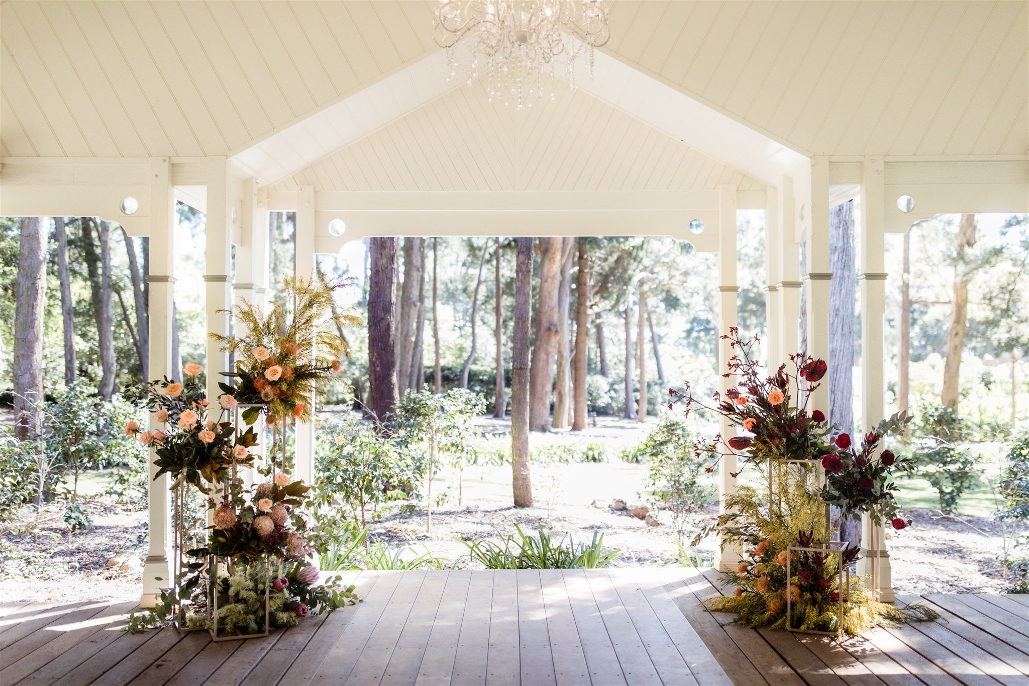 Pavillion set with a floral arrangement each side of a wedding aisle