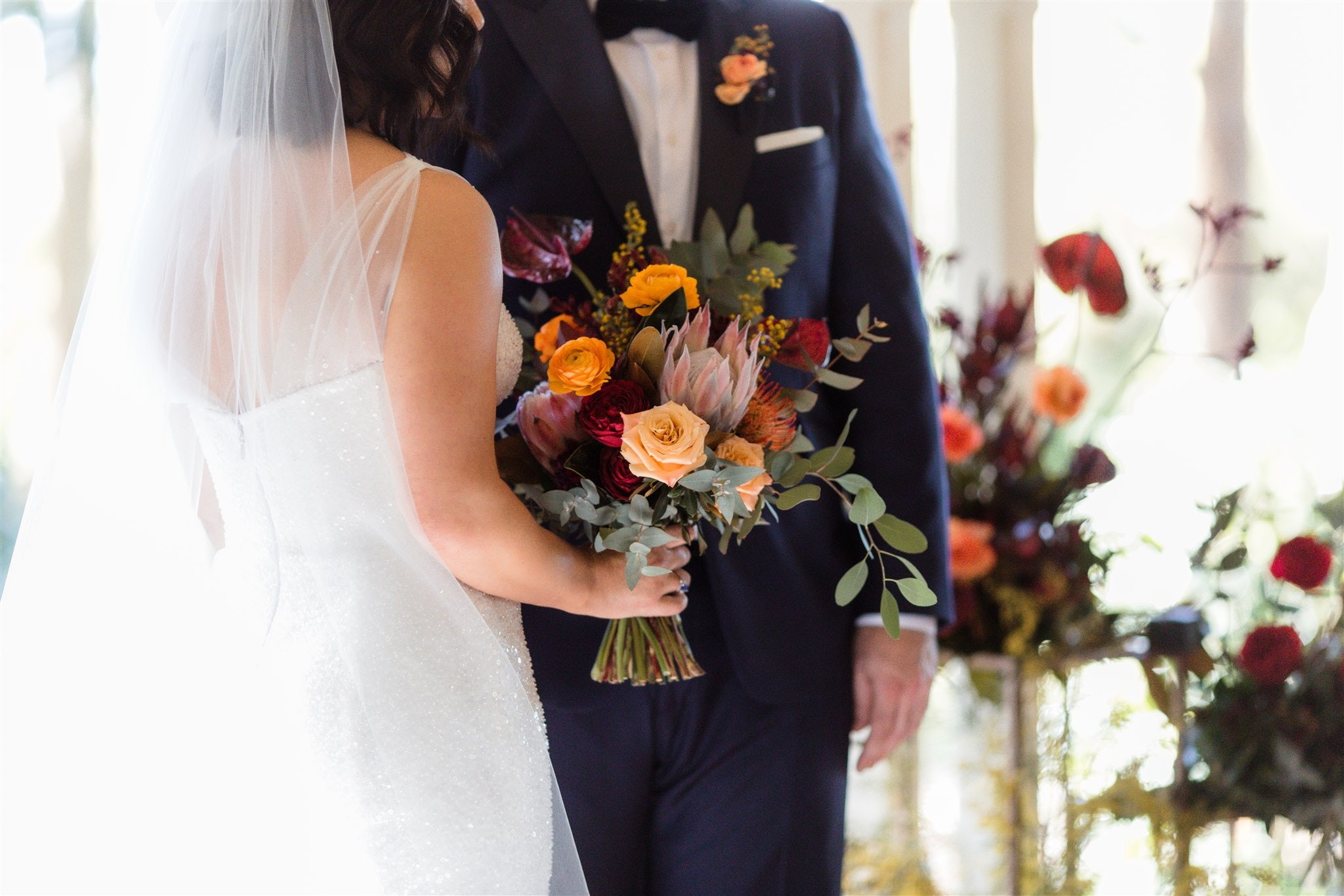 Bride standing next to groom holding bouquet