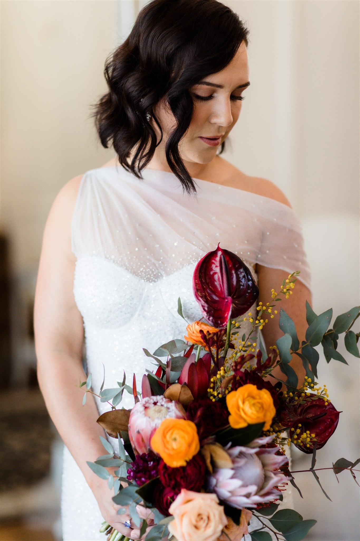 Bride holding bouquet looking away thoughtfully