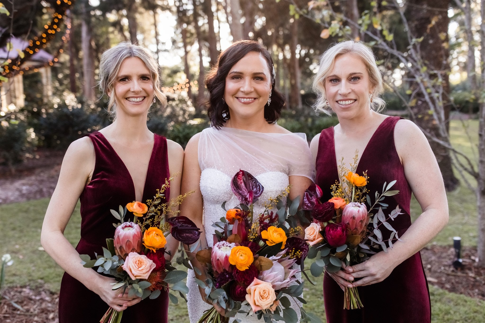 Bride standing in gardens with bridesmaids either side, holding bouquets