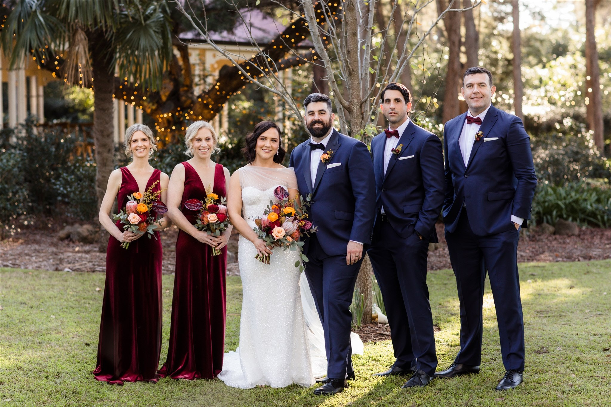 Bride and groom standing in gardens with wedding party