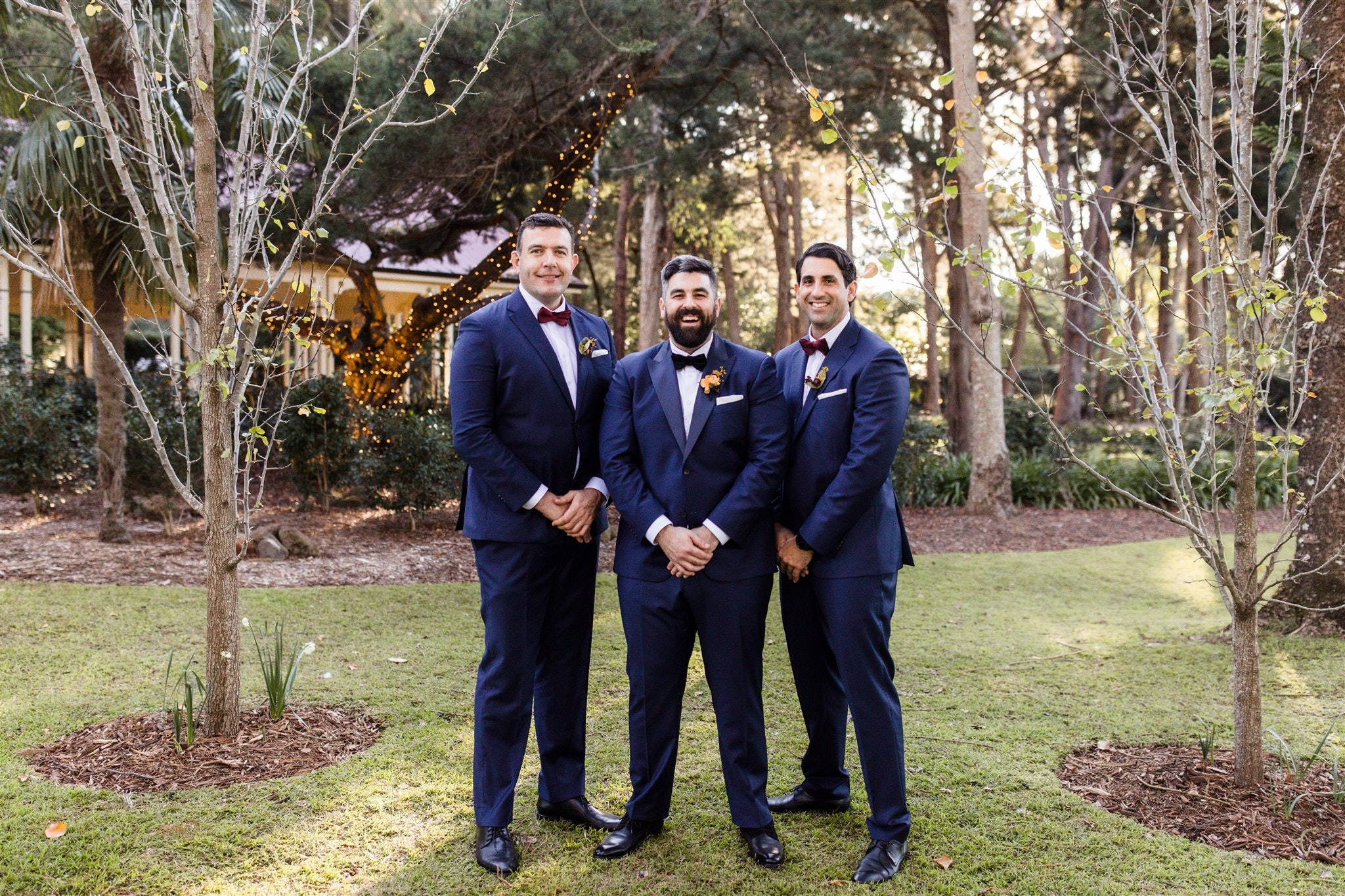 Groom and two groomsmen standing in gardens together