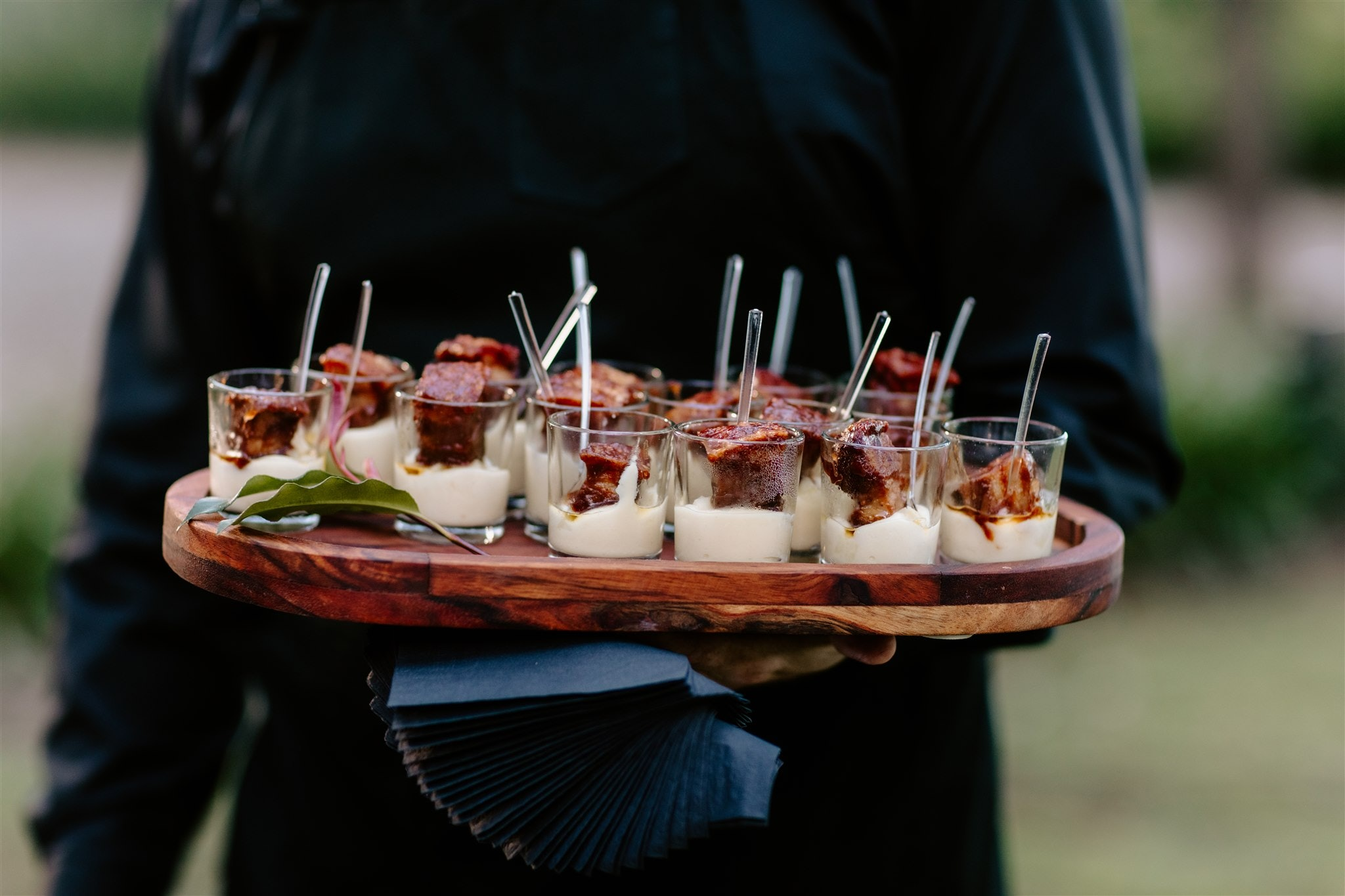 Waiter holding tray of pork belly canapes