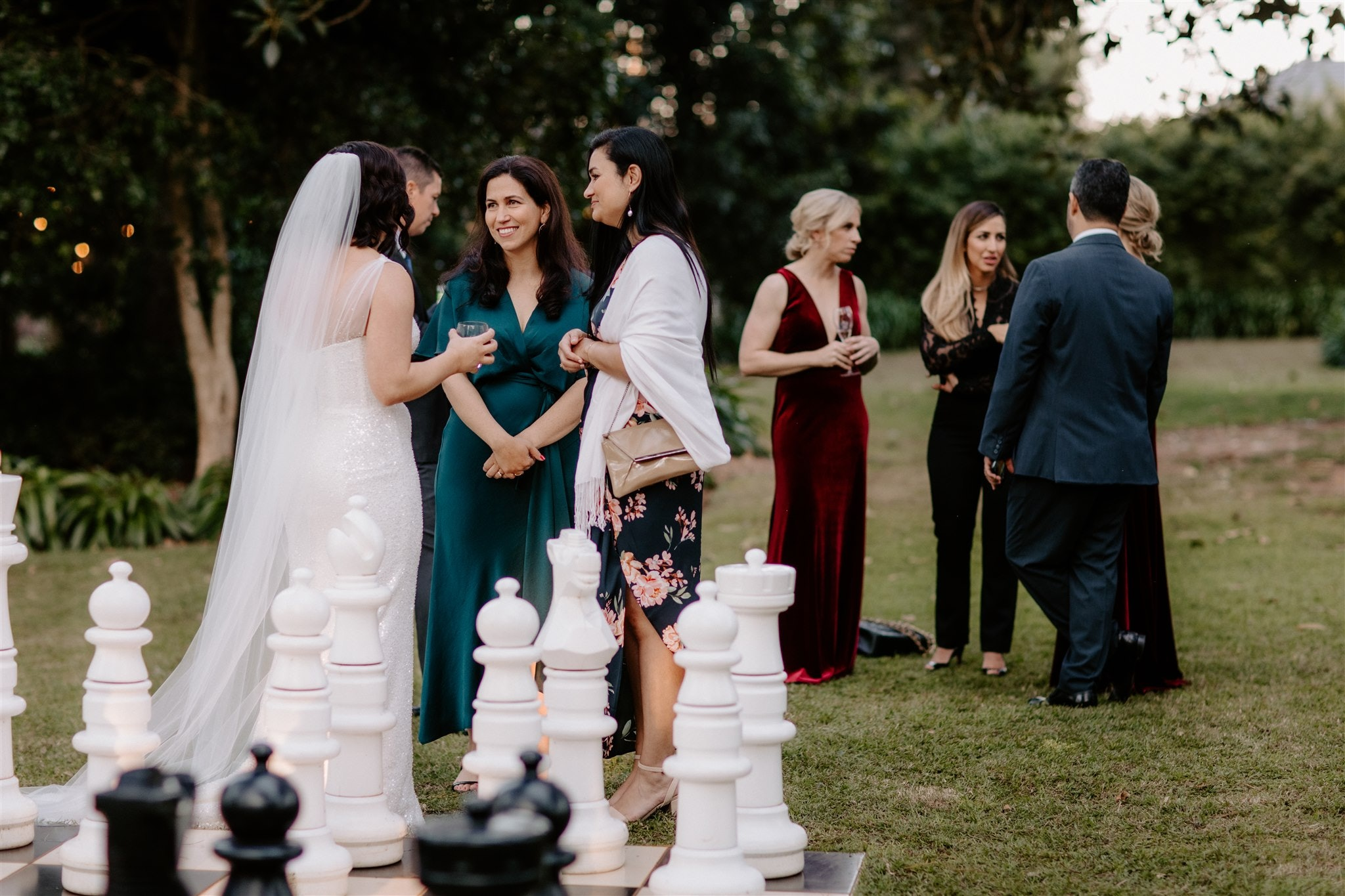 Bride standing near chess board talking to guests