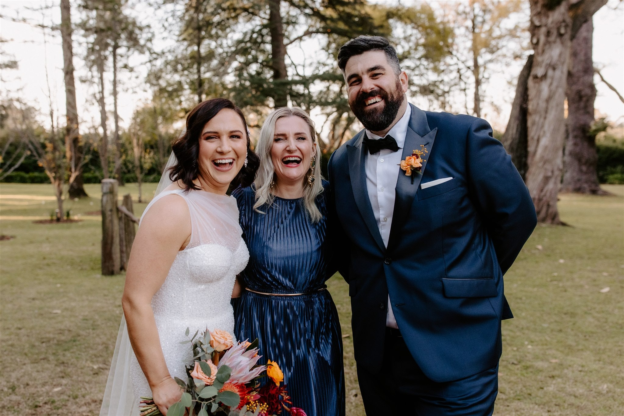 Bride and groom standing with friend laughing
