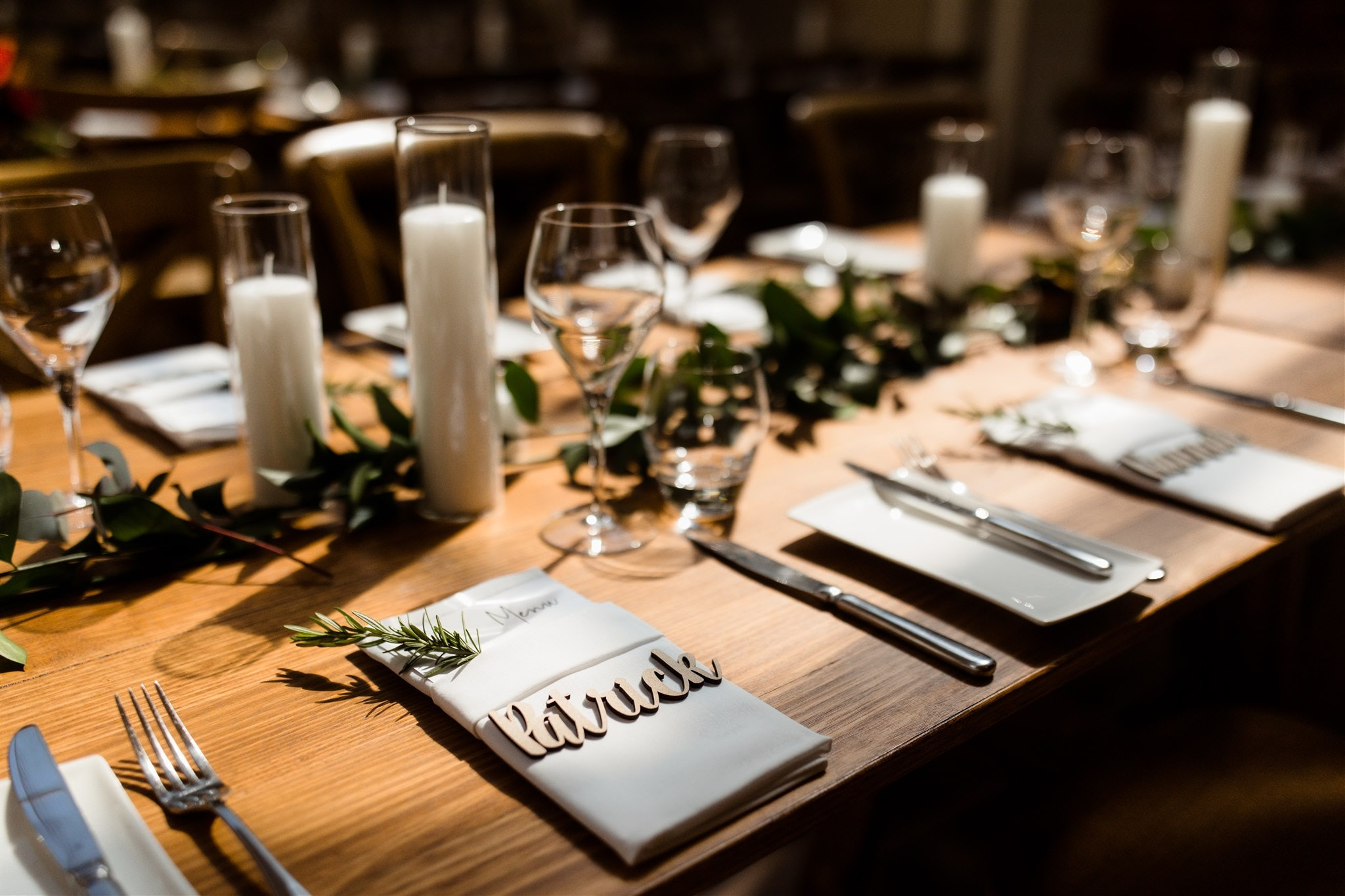 Wedding reception set with napkins, candles and greenery