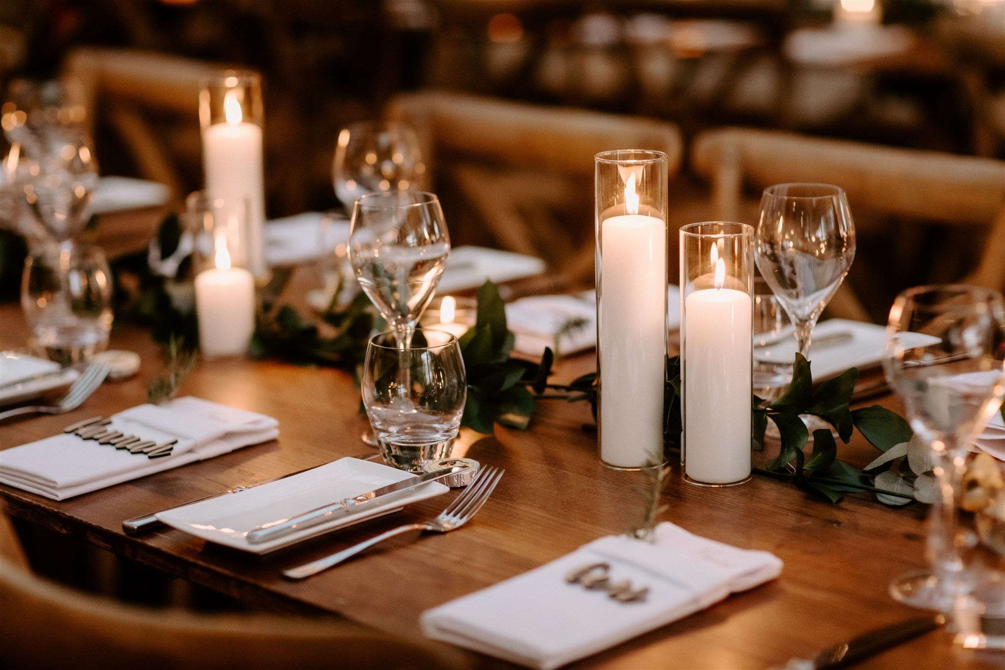 Wedding table set with candles, greenery and napkins