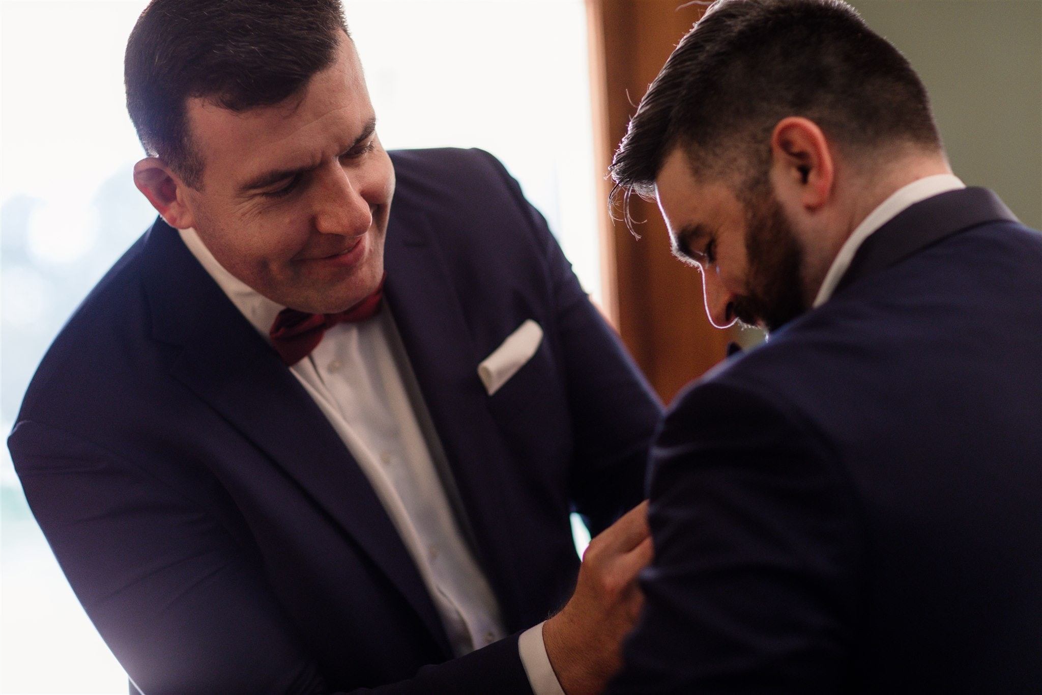 Groomsman pinning flower onto groom's jacket