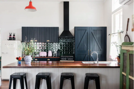 Kitchen with navy wooden cabinets, black rangehood and wooden benches