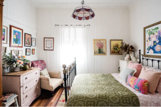Eclectic bedroom with green bedspread, leadlight pendants, pink distressed dresser and fresh cut flowers