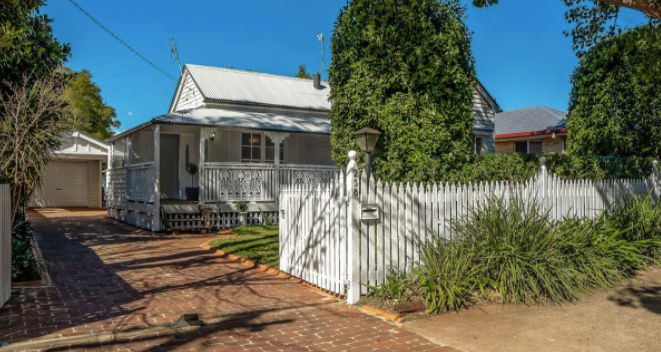 White cottage with white picket fence and porch