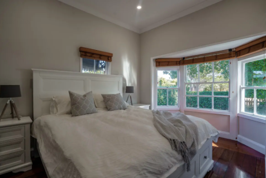 King bed in bedroom with bay windows