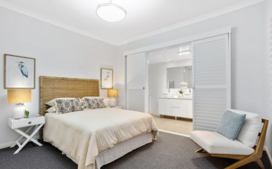 Bedroom with sliding plantation shutters and wooden rattan bedhead and blue styling features