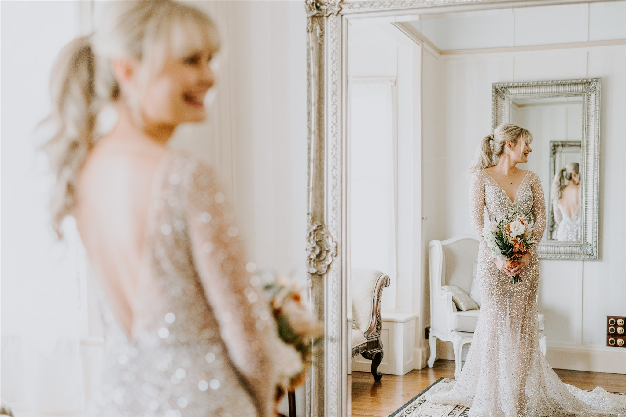 Bride in sequin wedding gown looks into ornate mirror