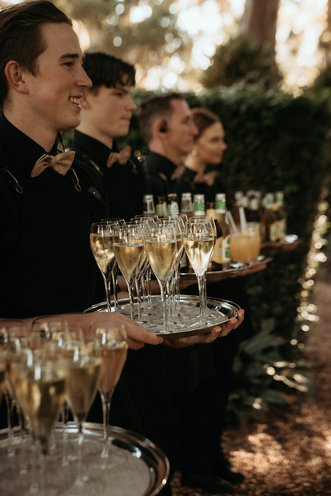 waiters dressed in black offer trays of champagne