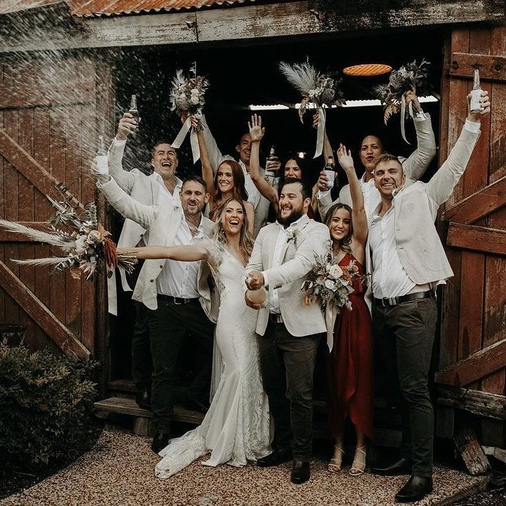 Bride and groom popping champagne with bridal party