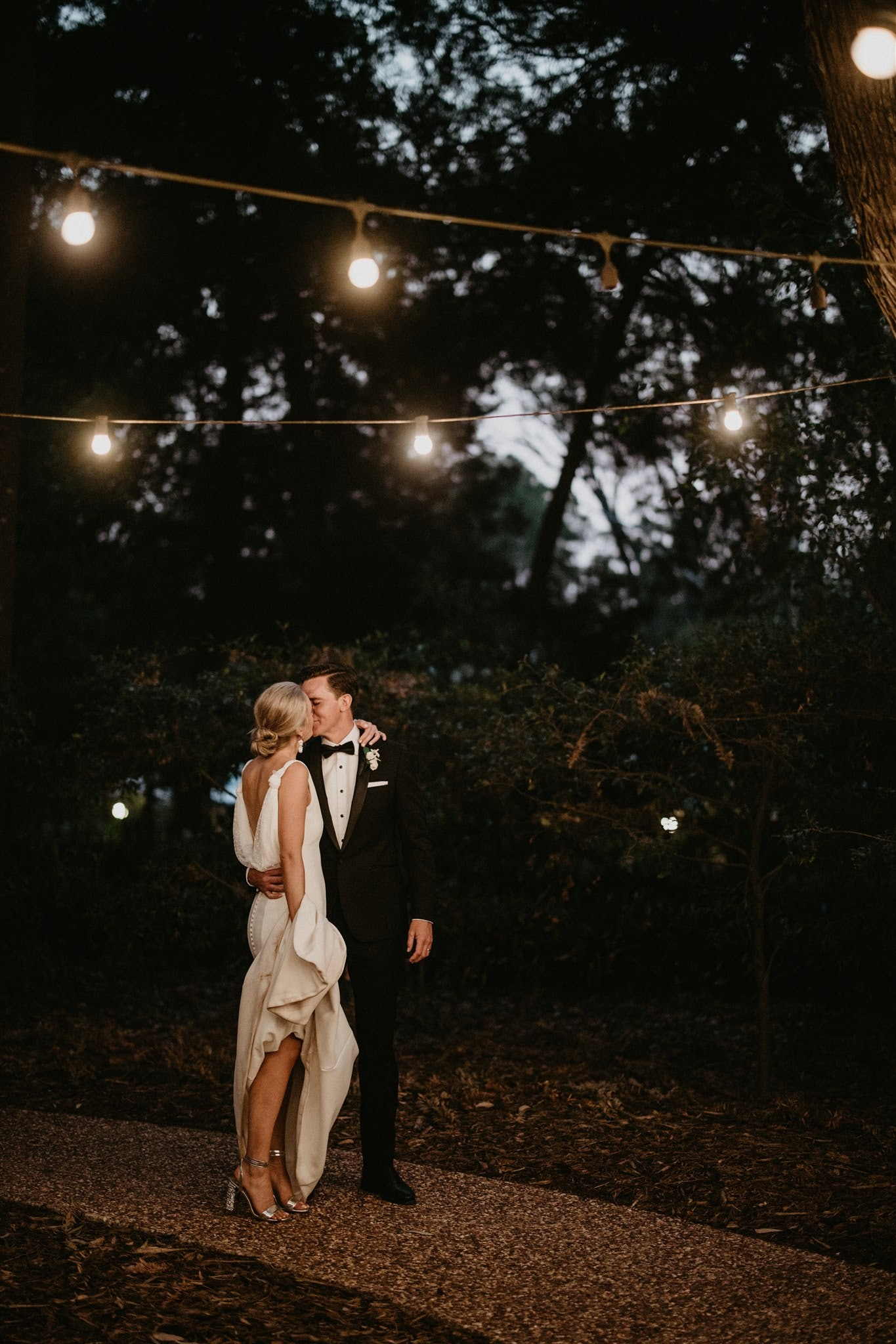 Bride and Groom kissing under festoon lights