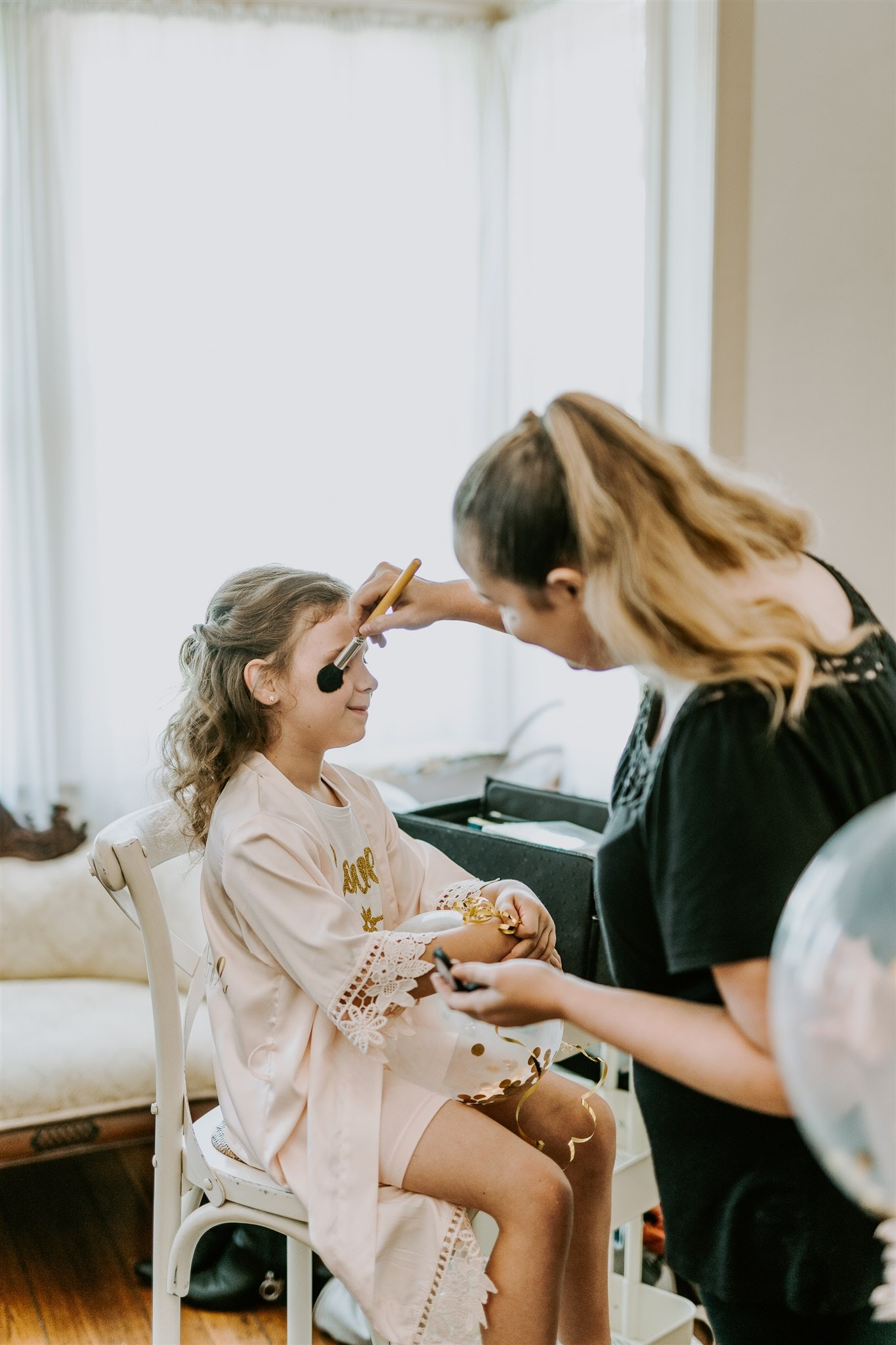 Flower girl getting make-up done