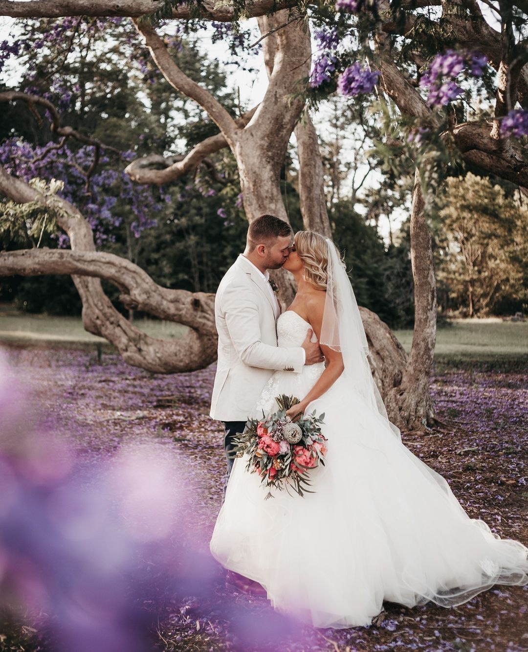 Bride and groom kissing under Jacaranda tree