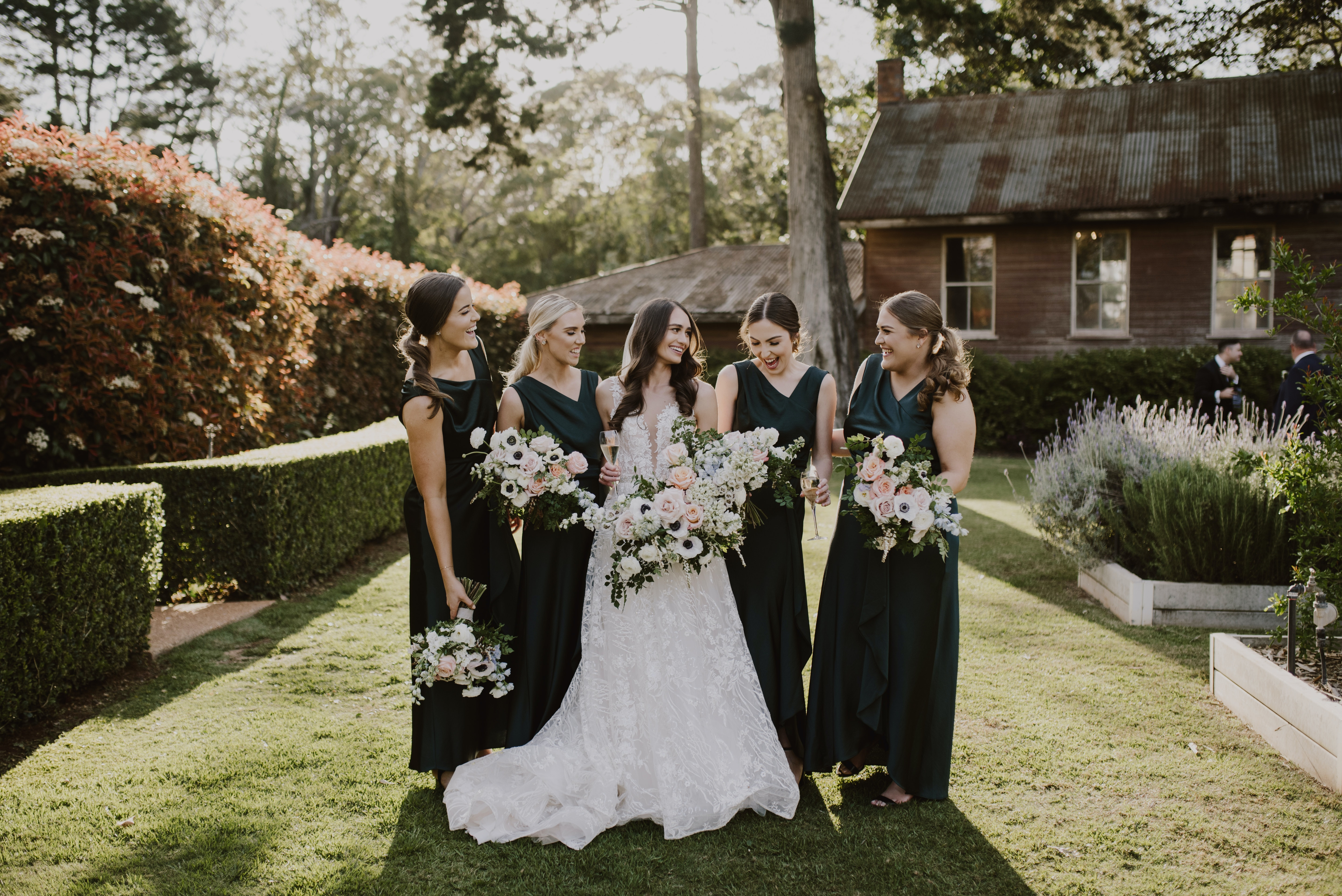 Bride with her bridesmaids in dark green dresses