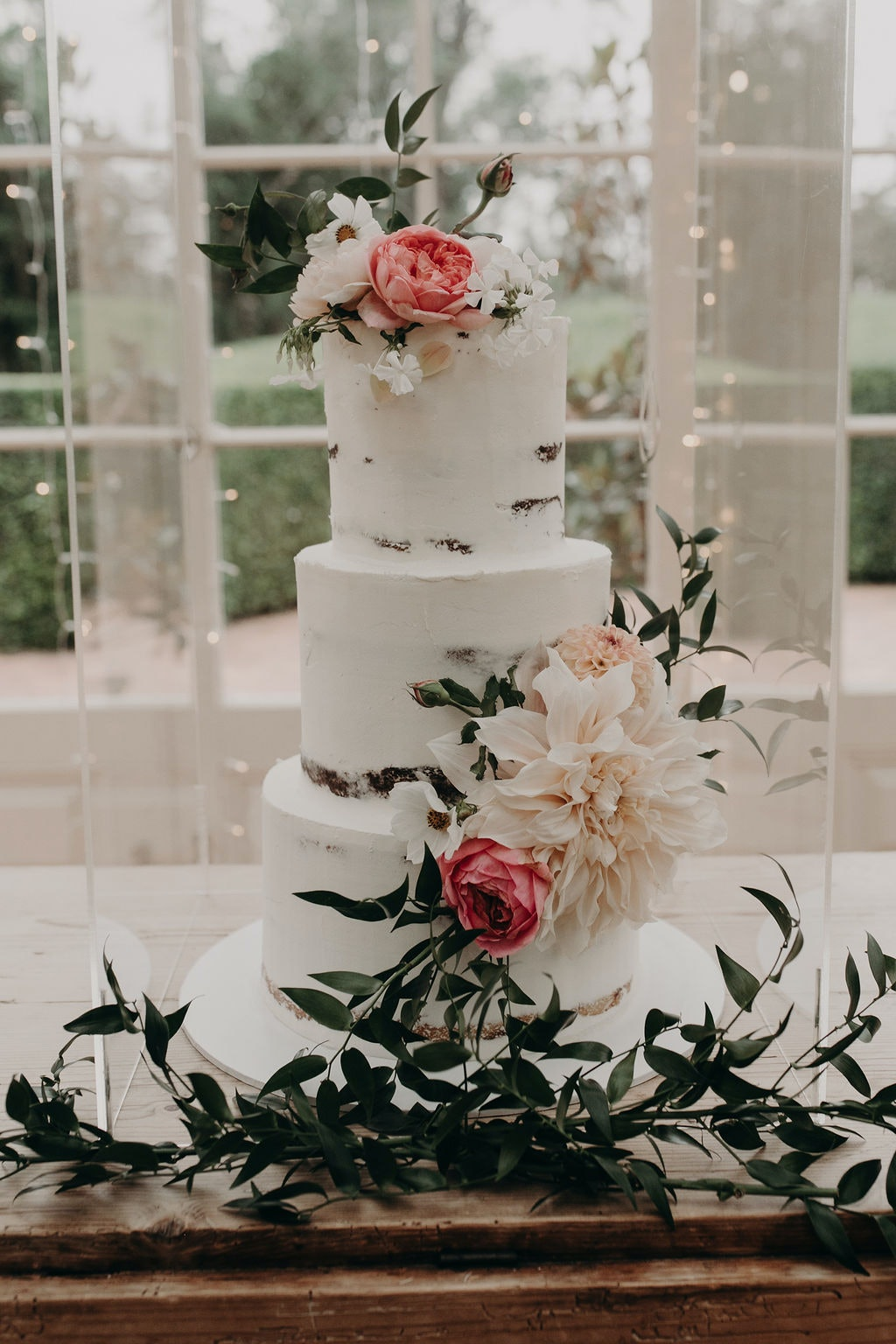 Naked wedding cake with white icing and fresh flowers