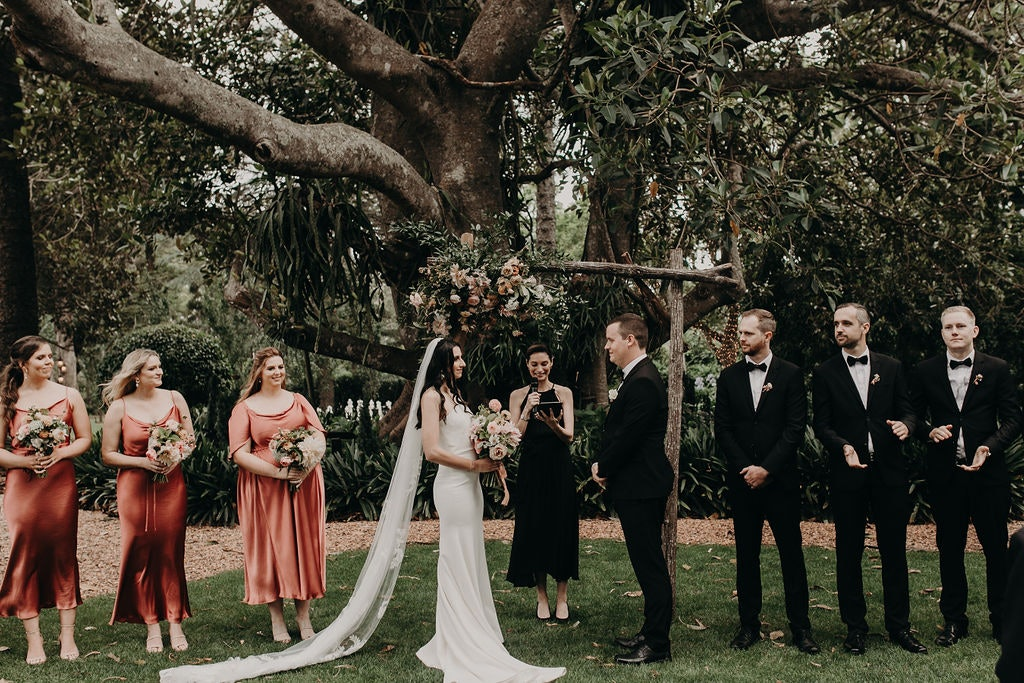 Bride and groom standing in front of arbour