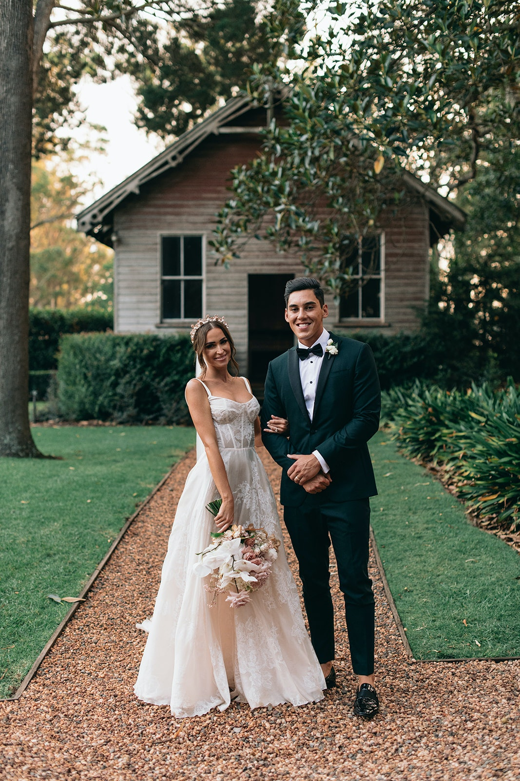 Bride and Groom standing in front of school house