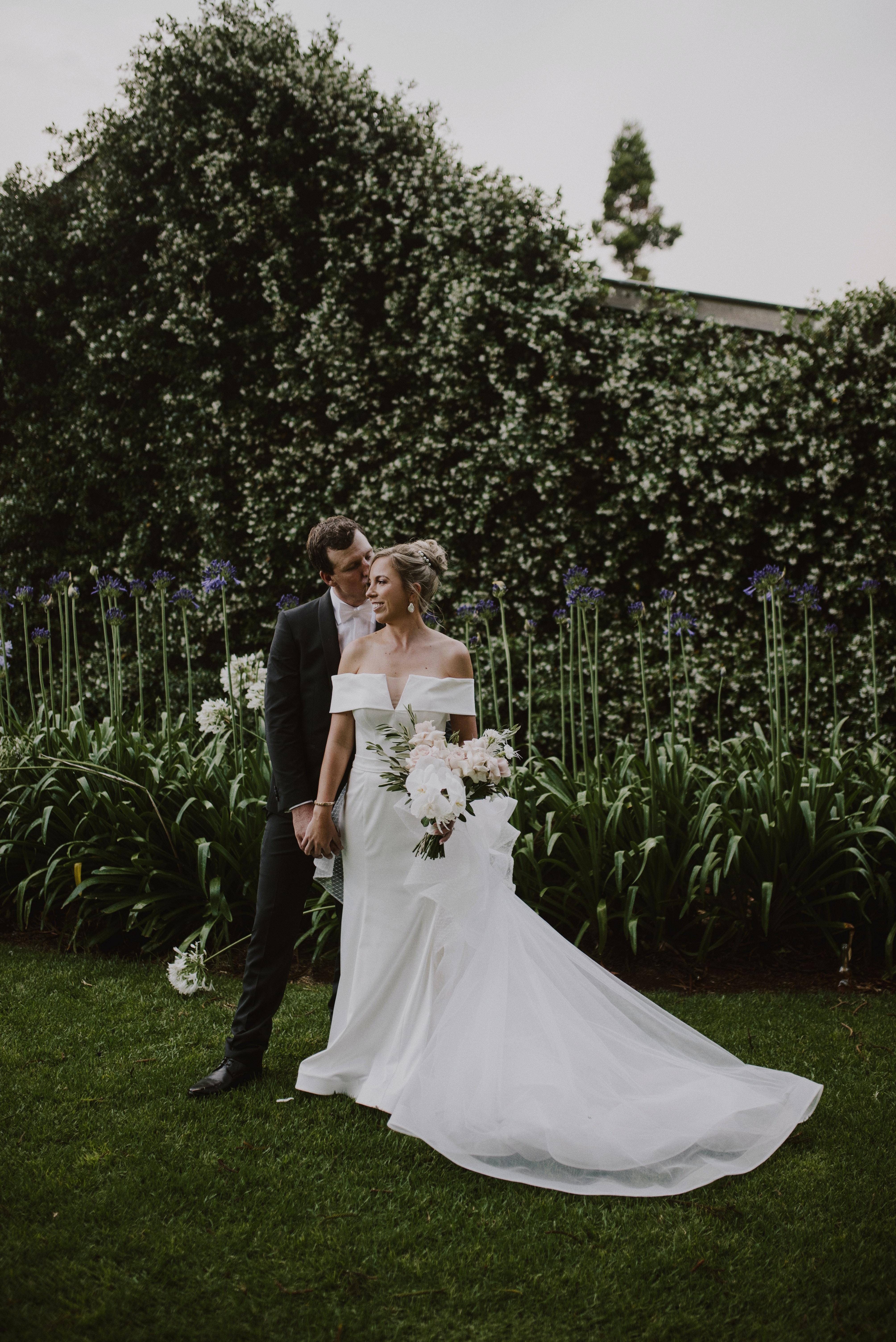 Bride and groom standing in front of jasmine vine kissing