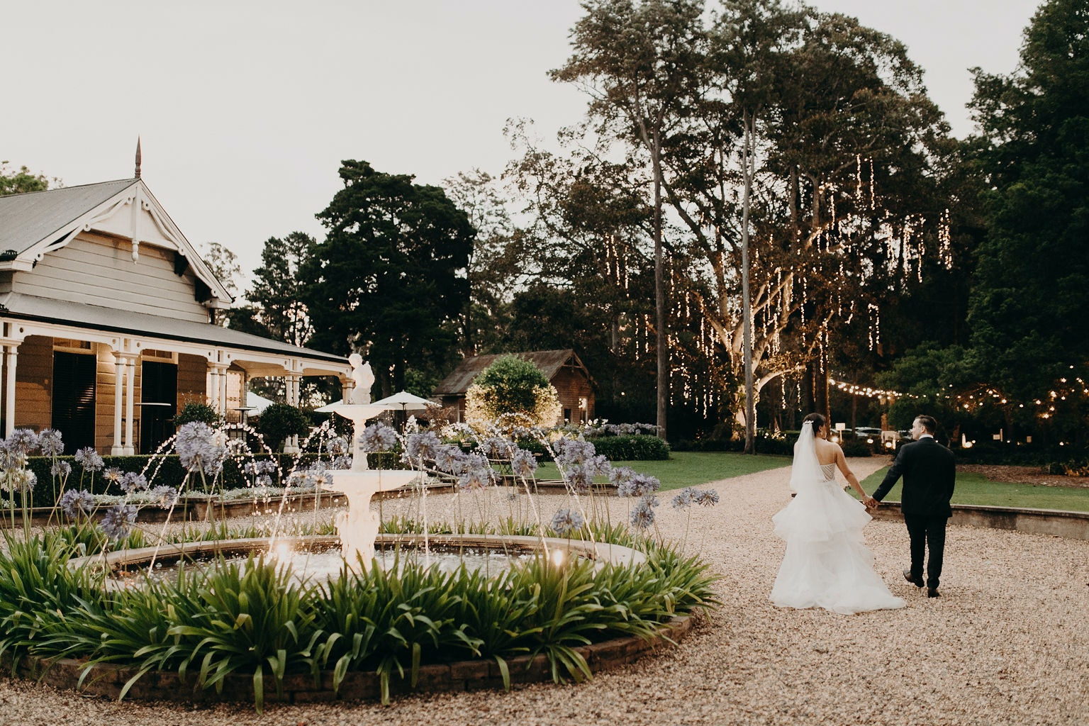 Bride and groom walking down stone driveway holding hands
