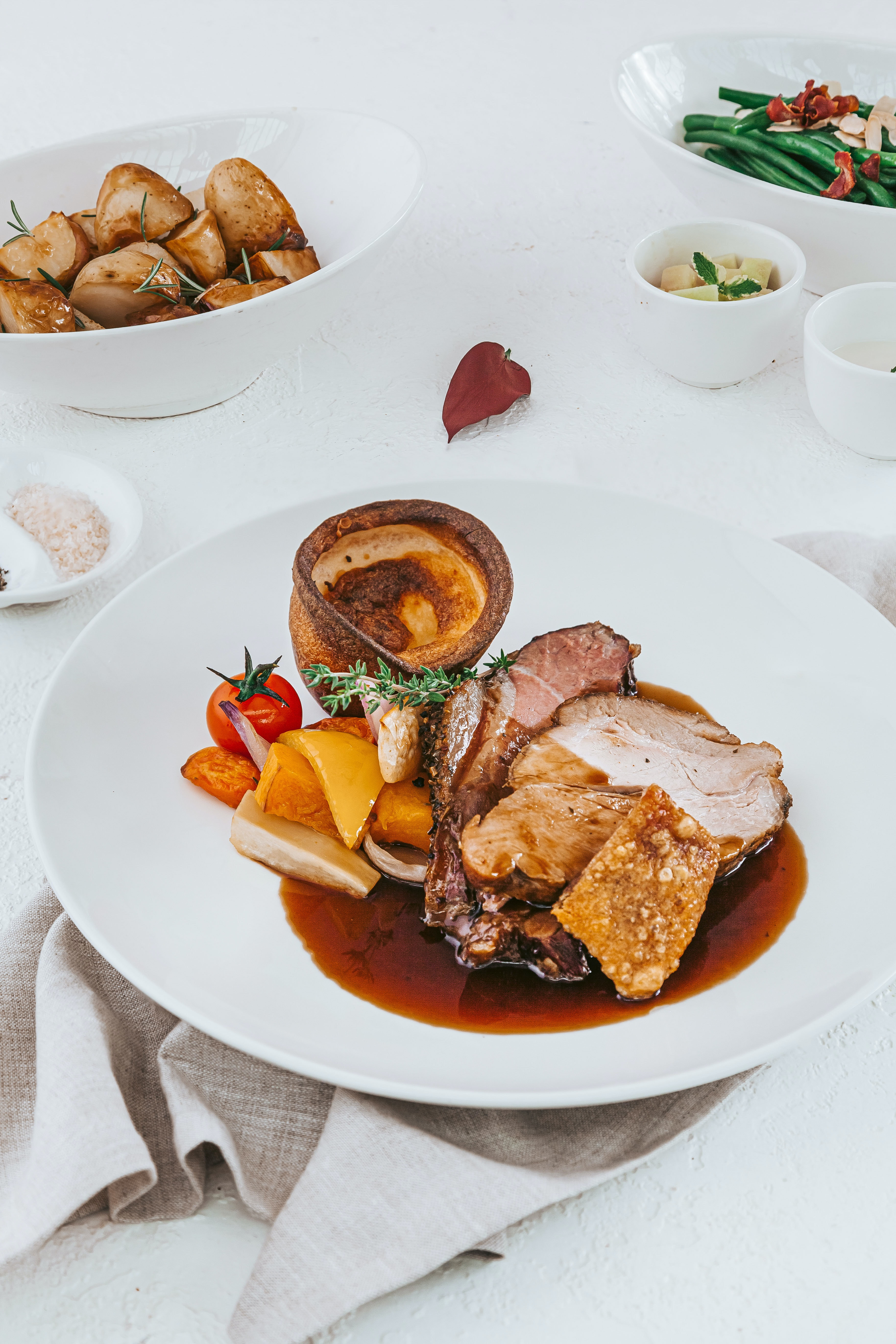 Roast pork served on a plate with Yorkshire pudding and gravy