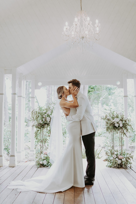 Bride and groom kissing at aisle