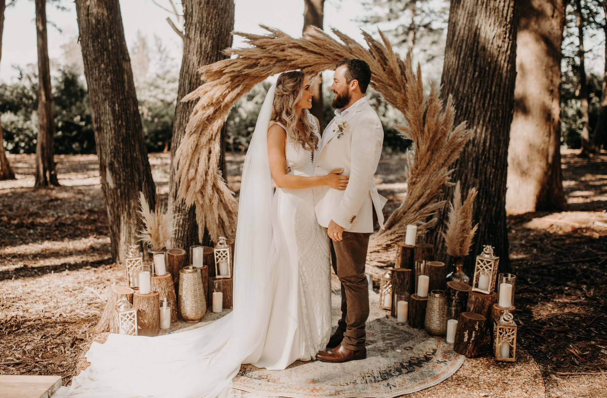 Bride and Groom standing in front of woodland arbour